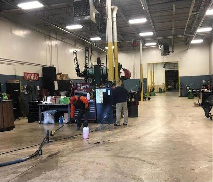 A warehouse with multiple stations that have workbenches and tool boxes. Floors are being cleaned by SERVPRO professionals.