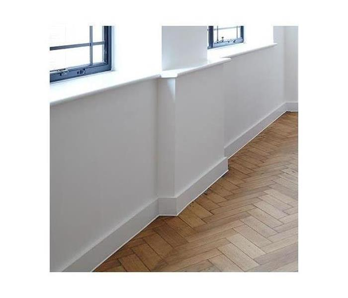 A brand new wall; white with white trim and new hardwood floors also.
