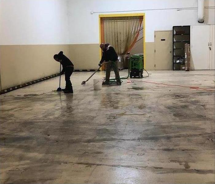 A warehouse with all the equipment removed, two SERVPRO employees cleaning the black soot off of the ground.