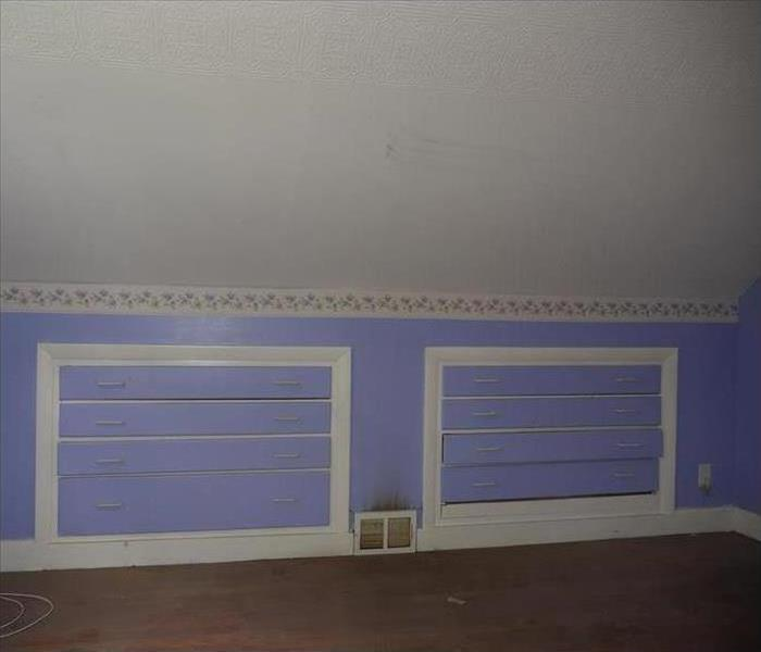 A purple bedroom with dresser drawers built into the wall, a heater in the center with blackened paint above it.
