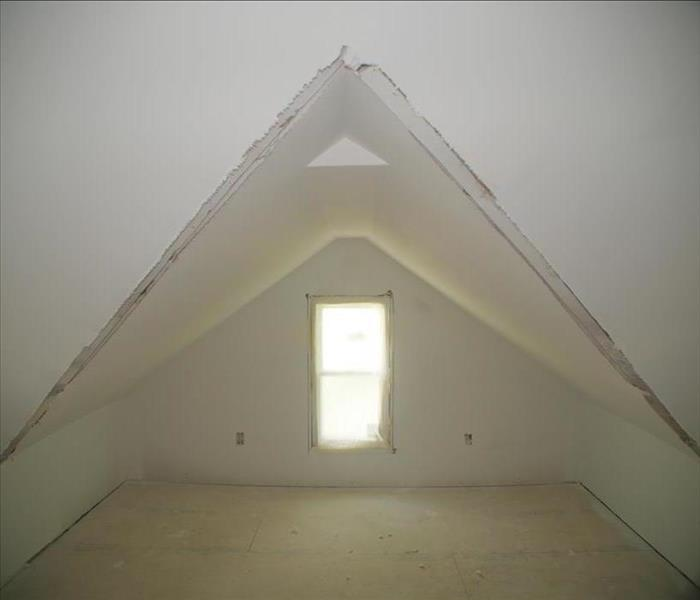 A small empty room with low ceilings, one window, fresh drywall, and floors