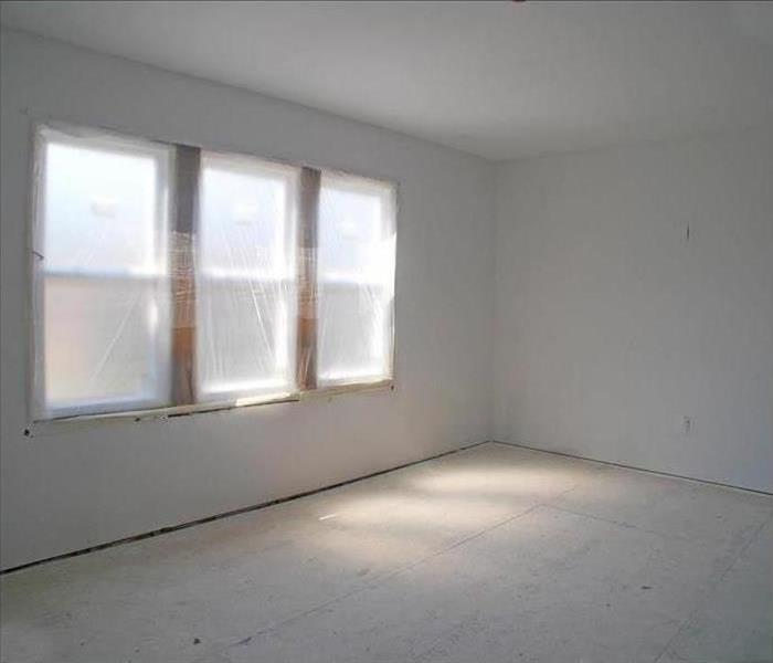 Bare room ready for finishing touches. Fresh dry wall, bare floors, new windows covered in plastic.