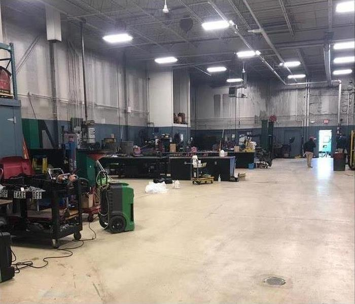 Warehouse fully repopulated with workbenches, clean floors, and industrial fans completing the drying process.