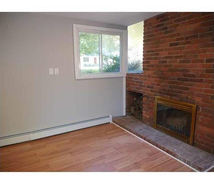 The same fireplace with a new window, hardwood flooring, and painted walls.