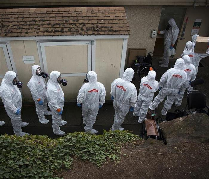 Servpro team entering building all in full body suits ready to handle virus