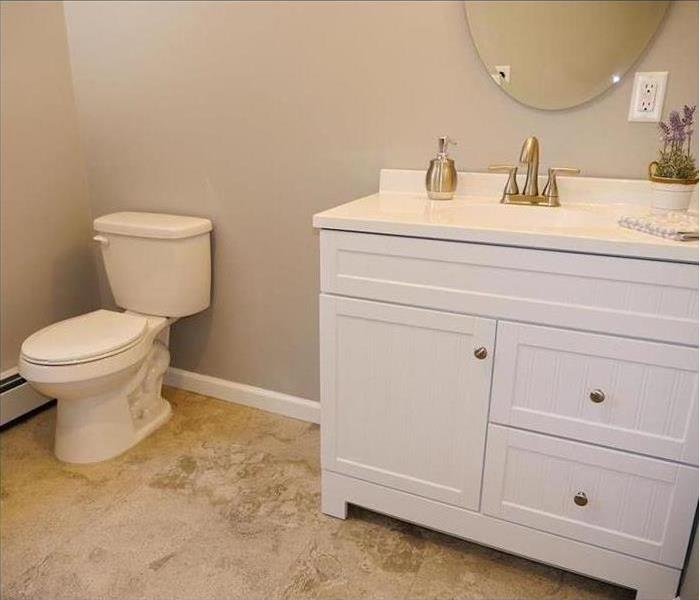 A finely finished small bathroom with new flooring, baseboards, toilet, sink with cabinets, and a mirror.