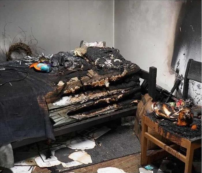 A bedroom that experienced a fire. Showing a burnt bed, wall, chair, and belongings.