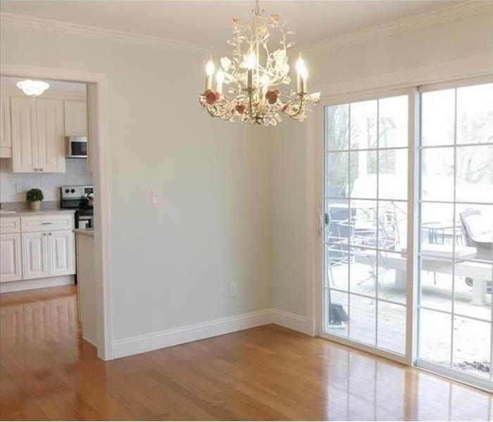 A nice dining room area with chandelier lights and glass door for a porch. Kitchen sink and stove partly visible