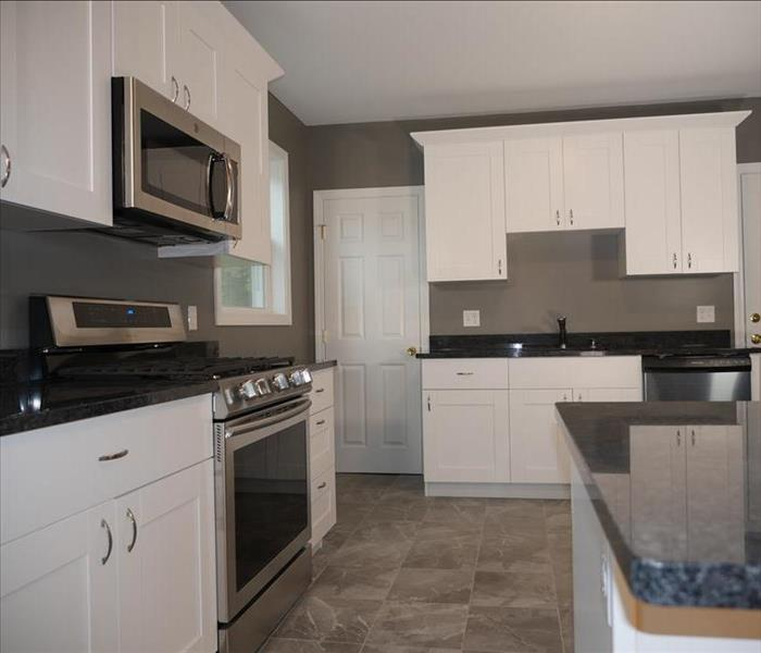 A new kitchen showcasing a new stove, microwave, and sink along with nice new cabinets & countertops.