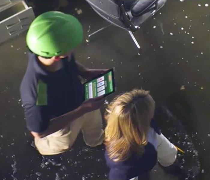 Woman showing SERVPRO employee around a flooded office.