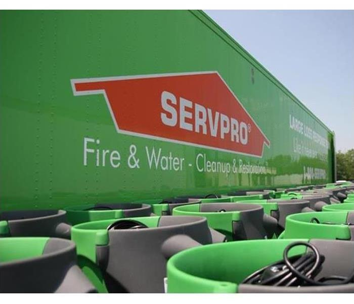 A large SERVPRO truck with many industrial sized fans lined up in front of it.