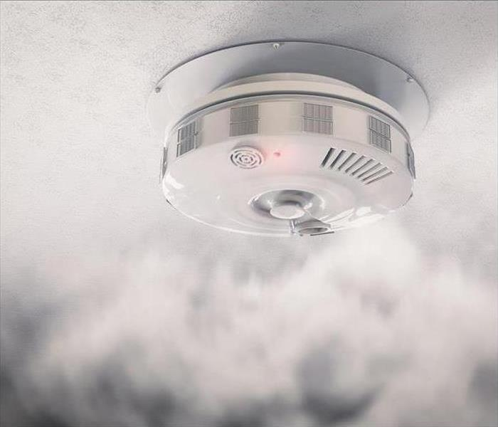 A smoke detector is surrounded by smoke