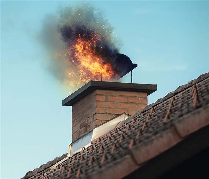 Flames shoot out of the top of a chimney.