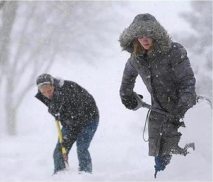 Two people shovel snow in a storm