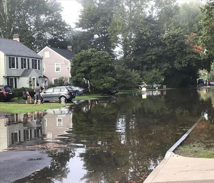 A street and homes are flooded with water from a burst sewer line