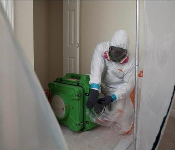 A worker wearing a protective mask and clothing cleans up mold.