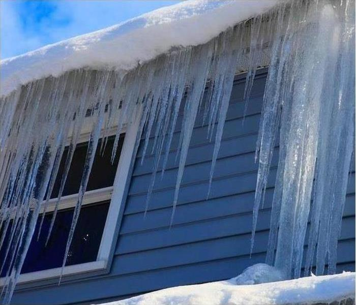 Icicles hang from the eaves of a house in winter