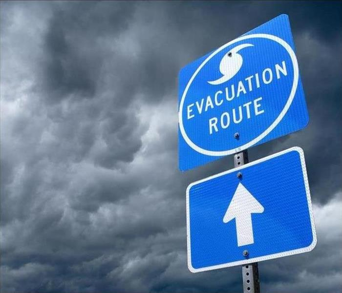 An evacuation sign in front of a stormy sky
