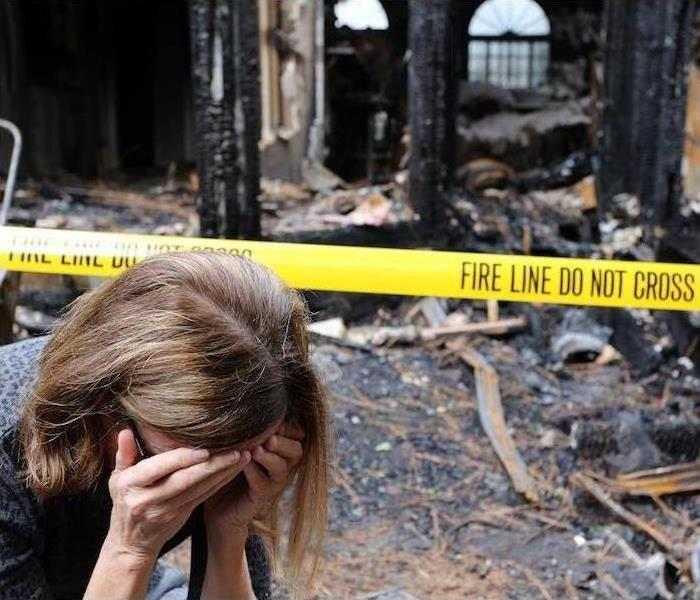 A woman holds her head in her hands in front of a burned-out house