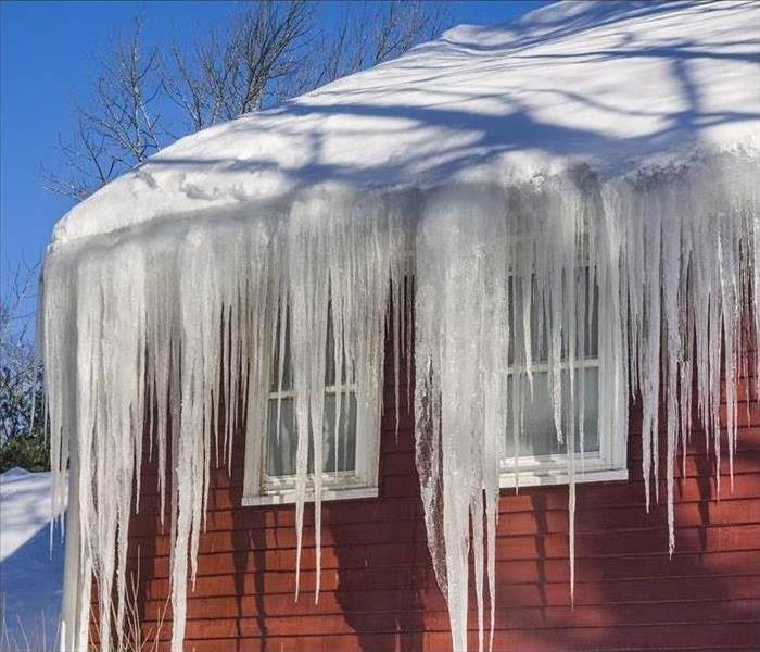Icicles hang from the roof and gutter of a home