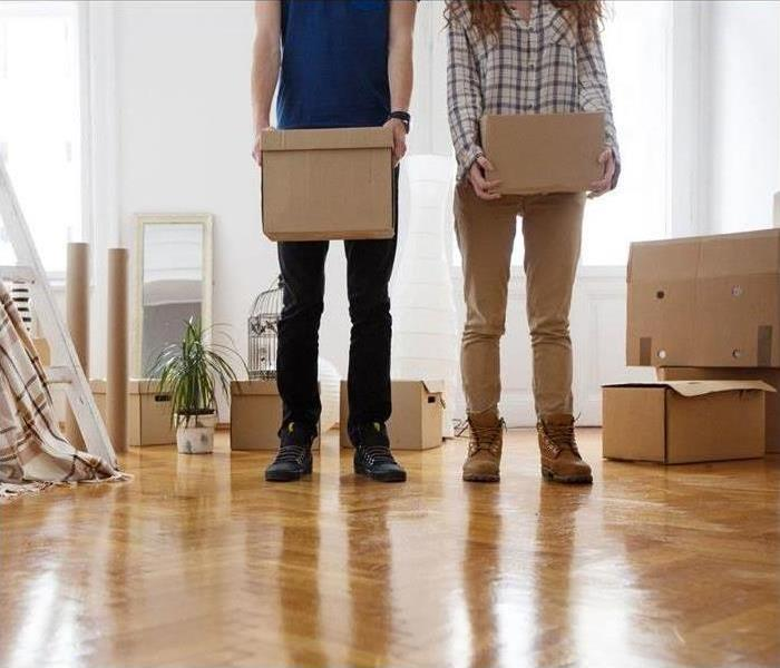 A man and woman stand among moving boxes